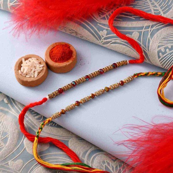 Pleasing stone studded Set of 2 Rakhi with besan ladoo,almonds and thali