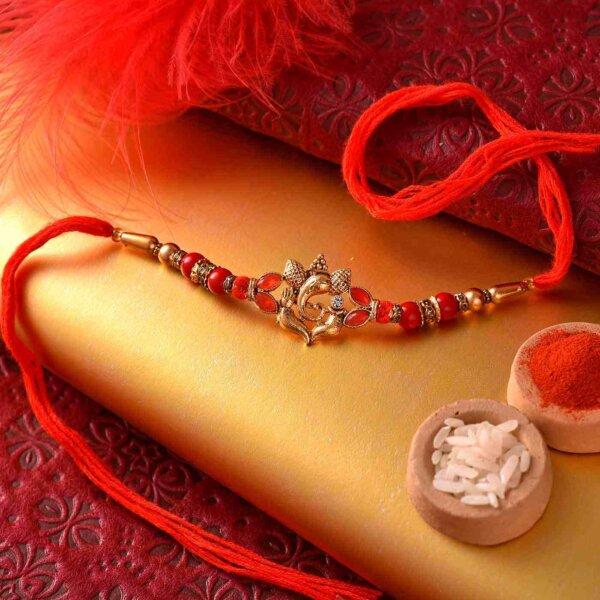 Kesar peda with golden ganesha and red beads rakhi.