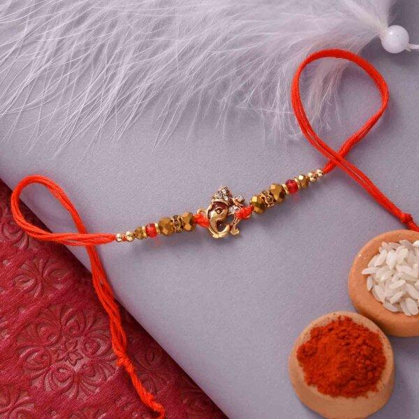 Mewa Bite with Antique Ganesha and Golden Beads Rakhi Set.