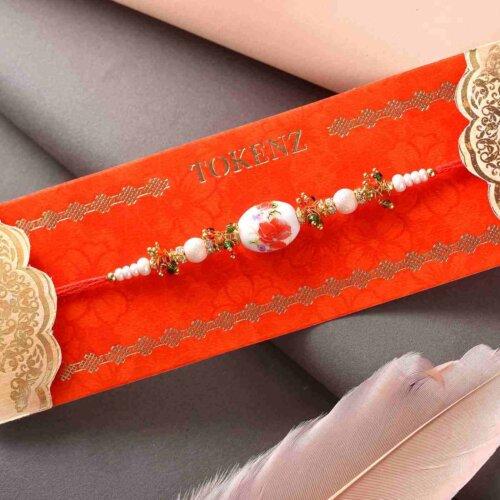 Stunning White Pearl Rakhi With Orange Touch