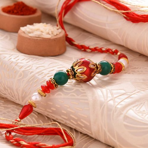 Conventional Red Pearl Rakhi With Dual-Toned Thread