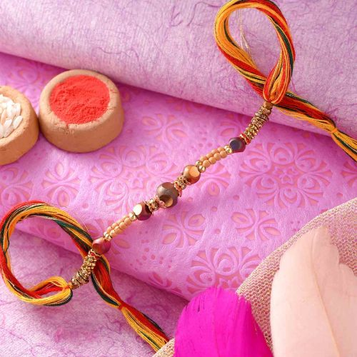 Golden Pearl Rakhi With A Multi-Toned Thread