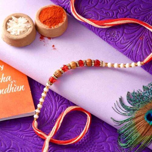 Maroon Beads Rakhi With A Dual-Toned Rakhi